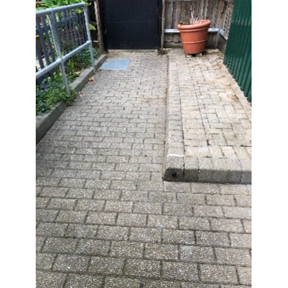 A clear and tidy paved area with no weeds growing between the bricks.
