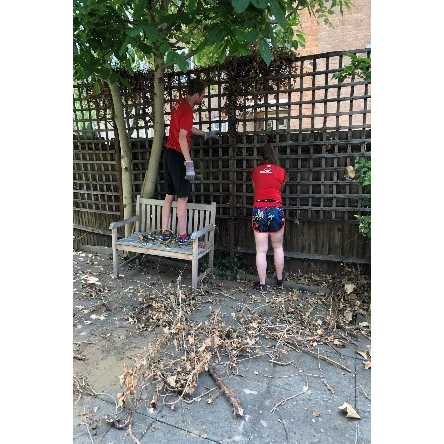 Two of the GoodGym runners pulling dead plants off a fence.