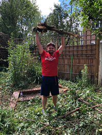 A GoodGym runner holding a branch proudly above his head, standing in a pile of discarded branches cleared from the garden area.
