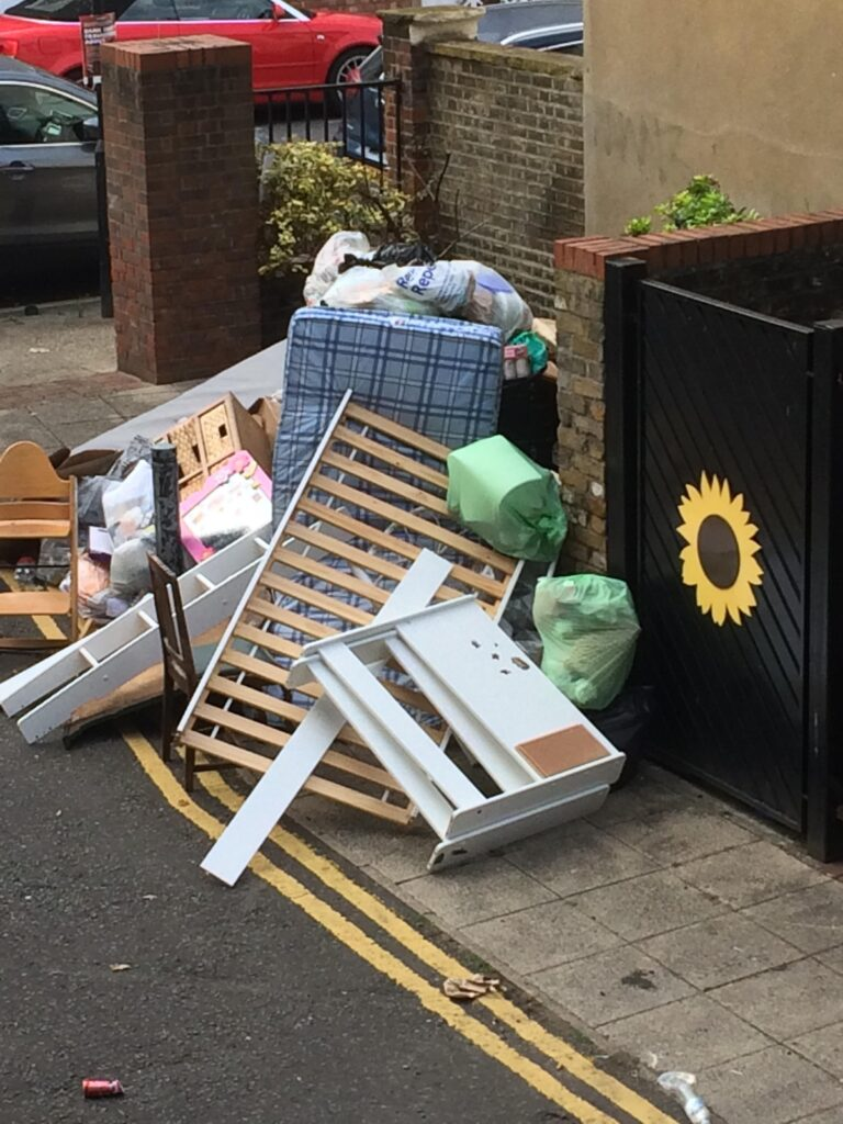 Example of fly-tipping: a bed frame, mattress and other rubbish by the side of the road