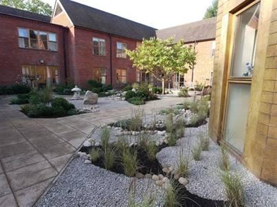 Smaller zen garden areas arranged around the outside of a paved garden area, with smaller stones and gravel instead of sand