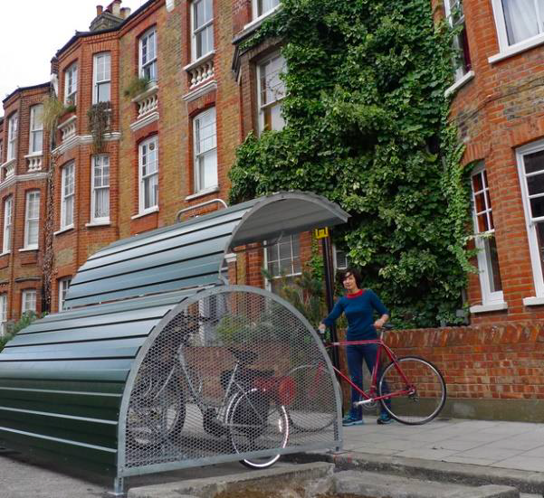 Semi-circular bike store with hinged cover beside a pavement